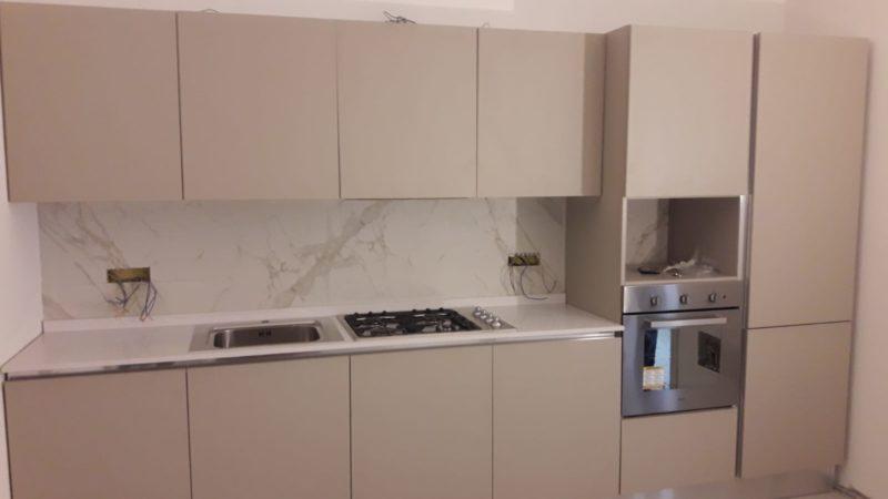 Cucina lineare in laminato grigio con top in Dekton Bianco.